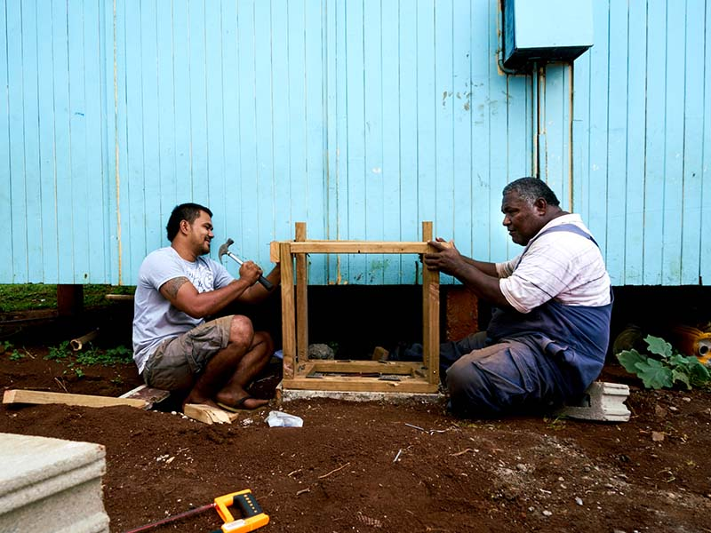 Our Projects Officer, Atalifo and Maciu the plumber building a shelter box for a new water pump.