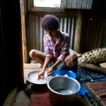 Soko prepares cassava, she cuts off the skin and chops it into large pieces, which are rinsed before being boiled in salt and water
