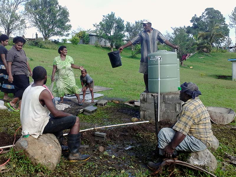 Community effort to set up the biosand filtration tank for two drinking stations.