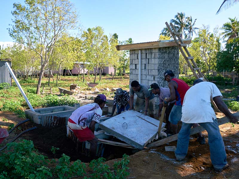 Lifting this heavy concrete lid requires teamwork. Able members of the community construct their pour flush toilet connected to two offset leach pits with guidance from our field staff.