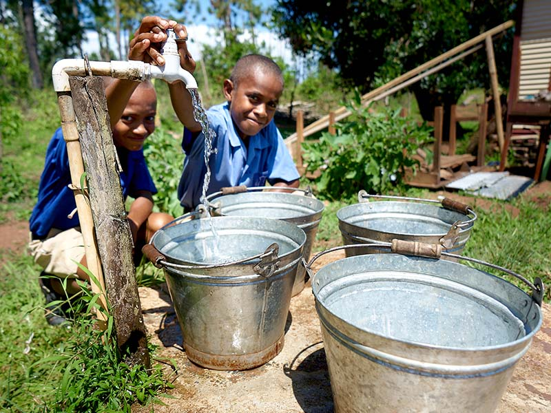 Paula Wame fill their water buckets at Cobue Sanatan Dharam Primary School. Thie school year has just begun and spring is underway.