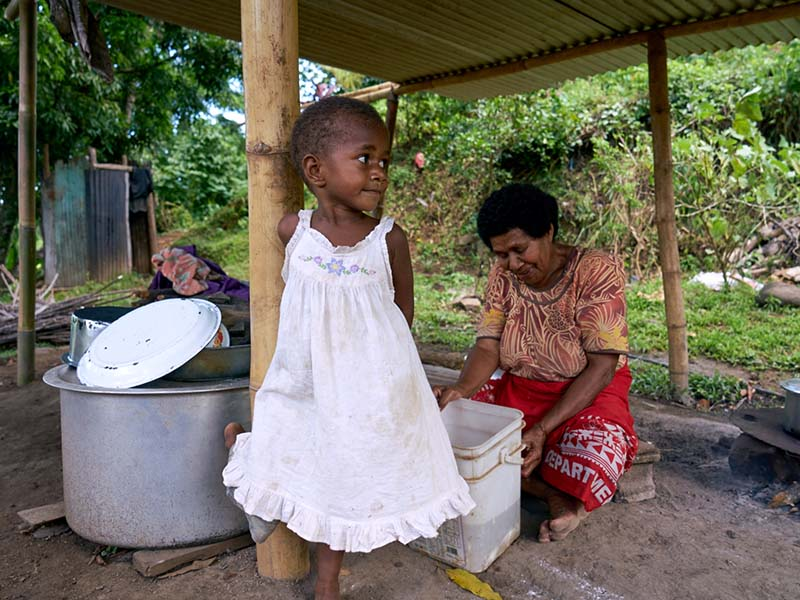 Mereoni fetches water while her grandmother prepares lunch