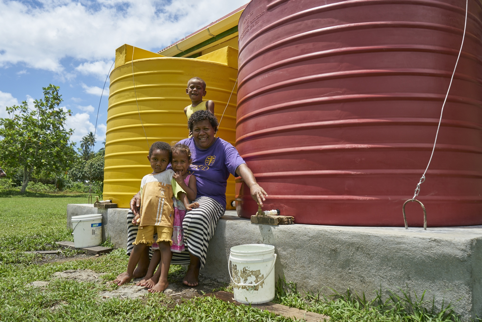 A women and her children enjoying the luxury of having safe rainwater supply .